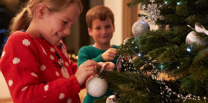 two-kids-decorating-holiday-tree_iStock